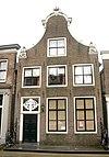 foto van Huis met klokgevel, voorzien van gebeeldhouwde afdekkingen in Lodewijk xv-stijl