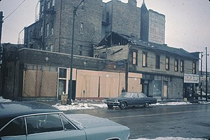 Old Town, Chicago - The former two story office and 'De Luxe Gardens' saloon on Sedgwick and North Avenues as photographed circa 1966 after a fire. A painted advertisement for Paddy Bauler as alderman can be seen in this photo on the wall above the building.