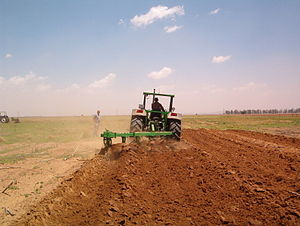 Plough - Modern tractor ploughing in South Africa. This plough has five non-reversible mouldboards. The fifth, empty furrow on the left may be filled by the first furrow of the next pass.