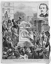 Un homme en chapeau dévoilant une tombe devant la foule