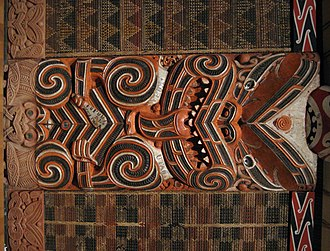 Tukutuku - Tukutuku panels flank a carving in a 19th-century meeting house.