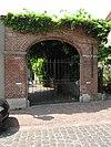 Grote gemetselde poort met pilasters en twee gedenksteentjes