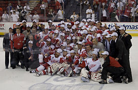 The Detroit Red Wings team, coaches, and support staff pose on the ice with the Stanley Cup.