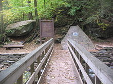 "View from a wooden footbridge with handrails over a rocky creek in a green forest. At the end of the bridge are a large boulder with a bench below it to the left, a trail sign labeled ""Waters Meet"" and ""The Falls Trail"" above a map of the trail in the center, and a natural stone monument with a metal plaque to the right."