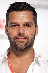 Ricky Martin, wearing a white shirt with an orange strip.