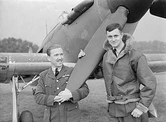 RAF Wittering - Flight Lieutenant M H Brown and Pilot Officer Chatham of No. 1 Squadron standing by the nose of a Hawker Hurricane Mark I at Wittering,. CH1566
