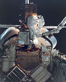 Mission Specialists George Nelson and James van Hoften repair the captured Solar Maximum Mission Satellite.
