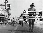 Sailors carrying wheel chocks across the flight deck of carrier USS Hancock (CVA-19), circa in 1966.jpg