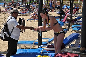 English: A woman wearing a bikini inspects a salesman's necklaces on a popular beach on a sunny day. Huatulco, Oaxaca, México.