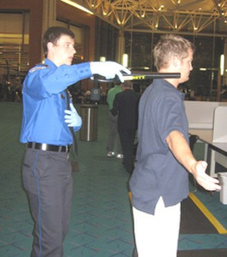 Transportation Security Administration - TSA agent screening a passenger.