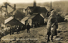 A young girl holds her younger sister on a hillside overlooking the Universal Colliery; a crowd, also waiting for news, are a little further down the hill.