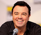 A man with short black hair and a black shirt sitting in front of a microphone, laughing.