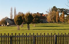 Stone buildings seen behind trees and grass area with wooden fence in the foreground.