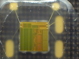 Smart card - 4 by 4 mm silicon chip in a SIM card, which was peeled open. Note the thin gold bonding wires and the regular, rectangular digital-memory areas.