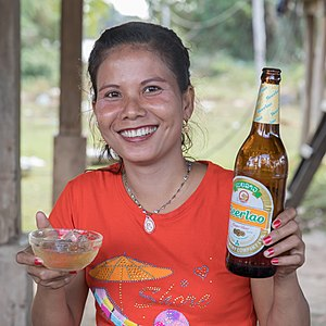 Smiling woman holding a cup and a bottle of beer
