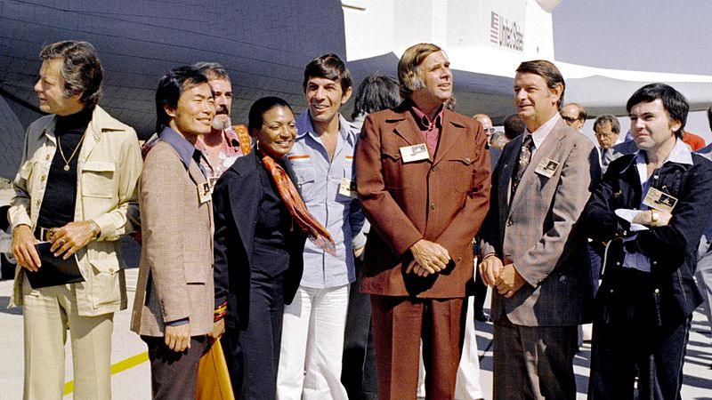 "The Space Shuttle Enterprise rolls out of the Palmdale manufacturing facilities with Star Trek television cast and crew members. From left to right, the following are pictured: DeForest Kelley, who portrayed Dr. ""Bones"" McCoy on the series; George Takei (Mr. Sulu); James Doohan (Chief Engineer Montgomery ""Scotty"" Scott); Nichelle Nichols (Lt. Uhura); Leonard Nimoy (Mr. Spock); series creator Gene Roddenberry; NASA Deputy Administrator George Low; and, Walter Koenig (Ensign Pavel Chekov). Wikimedia Commons: NASA"