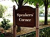 "A brown wooden sign with the words ""Speakers' Corner"" in white"