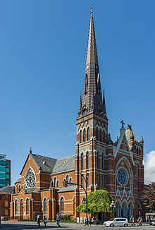 Exterior view of a red brick cathdral with a large spire built into a corner