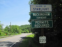 "Four signs on a green, metal pole against a background of greenery. The first, which is white with a blue border and lettering, reads, ""VILLAGE OF/STARLIGHT."" The second and third, which are both green with a white border and lettering, read, ""BUCKINGHAM/TOWNSHIP,"" and ""PERMITS/REQUIRED,"" respectively. The fourth, which is white with no border and black lettering, reads, ""SR 370/220."""