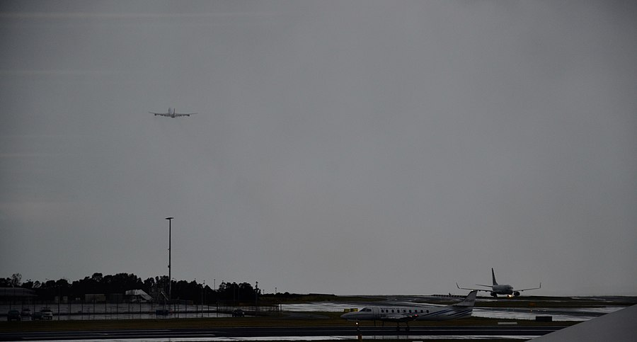 Sydney airport plane on ground and another into the clouds.jpg