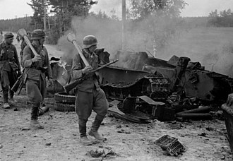 Finnish Defence Forces - Finnish troops equipped with Panzerfaust antitank weapons walk past a destroyed Soviet T-34 tank during the Battle of Tali-Ihantala. The lead soldier is also armed with a Suomi KP/-31.
