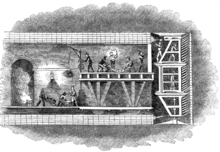 Illustration of a cross section through the Thames Tunnel showing miners on the platforms of a tunnelling shield digging at the face of the excavation whilst others behind on a wheeled platform construct the tunnel lining in brickwork