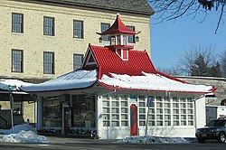 A white building with a red pointed and flared roof covered in snow.