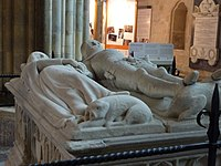 "The tomb of the Earl and Countess of Arundel in Chichester Cathedral, which is topped by a life-size sculpture of the couple. An unusual feature of the sculpture is central to Larkin's poem ""An Arundel Tomb"": ""Such plainness of the pre-baroque / Hardly involves the eye, until / It meets his left-hand gauntlet, still / Clasped empty in the other, and / One sees, with a sharp tender shock, / His hand withdrawn, holding her hand"""
