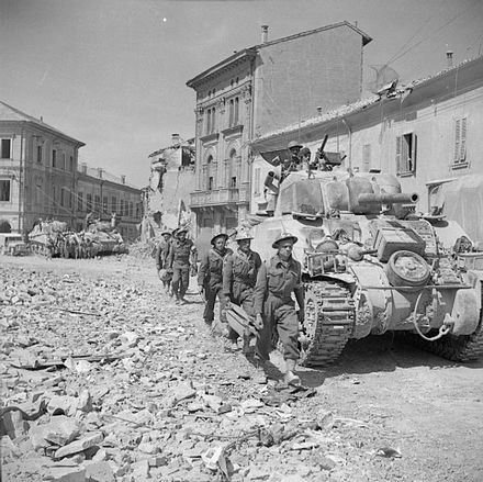 Stretcher bearers pass M4 Sherman tanks in Portomaggiore, 19 April 1945. The British Army in Italy 1945 NA24246.jpg