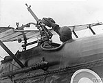 The Pilot of an S.E.5a of No. 1 Squadron putting a fresh double drum of ammunition on his Lewis Gun.jpg