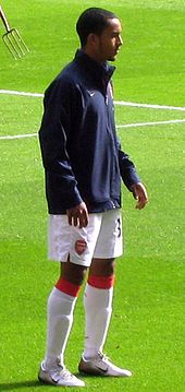 A man in a football uniform, warming up before a football match
