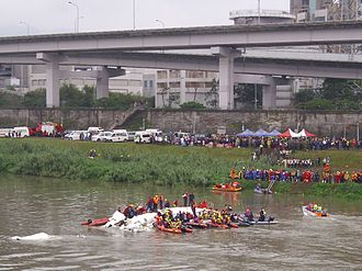 TransAsia Airways Flight 235 - The aircraft in the Keelung River under rescue, Huandong Viaduct in background