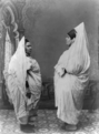 Two Jewish women standing, facing each other, in Tunisia.png