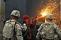U.S. Army Pvt. Cody Bowman, second from left, and Spc. David Renlund, center, team up to burn through a steel door during subterranean training at an underground training facility of West Fort Hood, Texas 131121-A-OB963-039.jpg