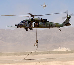United States Air Force Warfare Center - An HH-60G Pave Hawk retrieves a pararescueman as an A-10 Thunderbolt II provides cover fire during a firepower demonstration on the Nellis bombing range.