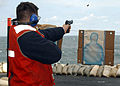US Navy 031022-N-6653C-001 A sailor shoots a 9mm pistol for small arms qualification on elevator three as part of the ship's force protection aboard USS George Washington (CVN 73).jpg