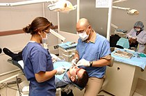 US Navy 040227-N-0000W-057 Navy Dental Officer Lt. Raul Barrientos, right, a native of El Salvador, provides care to a patient at U.S. Naval Dental Center (USNDC) Far East.jpg