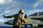 US Navy 040712-N-7732W-341 An Aviation Boatswain's Mate Handler directs an F-A-18C Hornet from the Stingers of Strike Fighter Squadron One One Three (VFA-113) towards one of four steam driven catapults onboard the aircraft carr.jpg