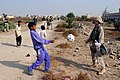 US Navy 041105-M-0095Z-009 Hospital Corpsmen 3rd Class Tarren C. Windham kicks a soccer ball around with an Iraqi child in Ad Diwaniyah, Iraq.jpg