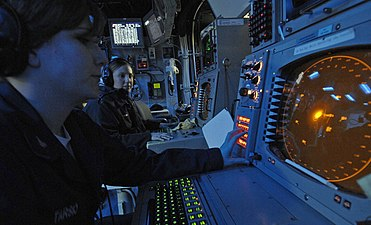 US Navy 061216-N-5345W-038 Operations Specialist 2nd Class Carly King watches as Operations Specialist 3rd Class Ashley Tarsio works at her Advanced Combat Direction System (ACDS) console in the Combat Direction Center (CDC).jpg