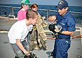 US Navy 110324-N-AW702-006 Damage Controlman Fireman Joe Hellow explains the importance of Mission Oriented Protective Posture (MOPP) gear to Rafea.jpg