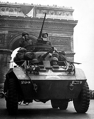 "Wehrmacht forces for the Ardennes Offensive - An American M8 armored scout car in front of the Arc de Triomphe at the ""Liberation Day"" parade in Paris."