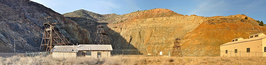 Panorama of fenced-off pit surrounded on three sides by rock walls. Three headframes and two buildings are within the enclosed area near the pit.