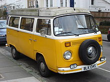 A yellow and white Vokswagen Type 2 vehicle, at center, is parked on a street. The roof of the vehicle is dirty, and on the sides of the picture, several other vehicles and buildings can be seen located on the street.