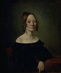 Portrait of a girl in a black dress sitting at table