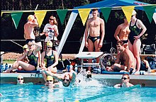 Swimmers posed in a group shot around the edge of a pool