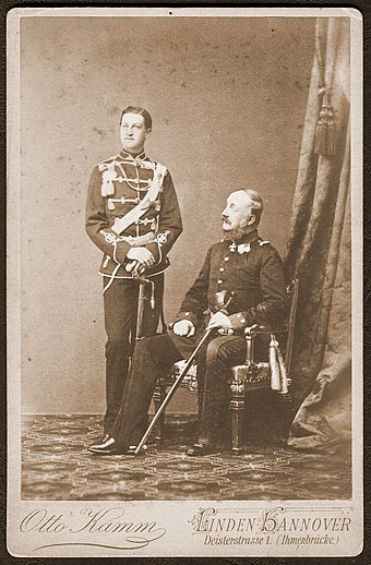 "The young crown prince with his father in the 1860s in ""Linden-Hannover"" 1860er Atelieraufnahme Ernst August, Kronprinz von Hannover, mit seinem Vater Konig Georg V., Kabinettformat, Fotograf Otto Kamm, Linden-Hannover, Deisterstrasse 1 (Ihmenbrucke).jpg"