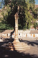 A picture of a small monument in front of a large, crooked tree, with a row of small houses in the background.