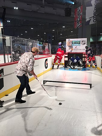 A NHL fan exhibit, where visitors attempt to deflect the puck off the skaters in front of the goalie in order to score 2016 NHL All-Star Game (24660199222).jpg