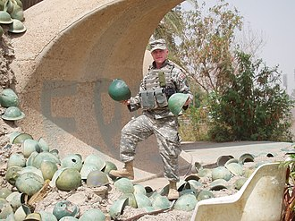 Victory Arch - An American soldier poses with the historical helmets at the base of the Victory Arch